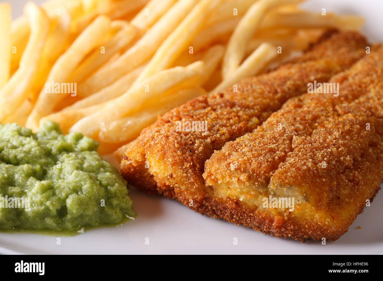 English food: fried fish fillets and chips and pea puree macro. horizontal - Stock Image