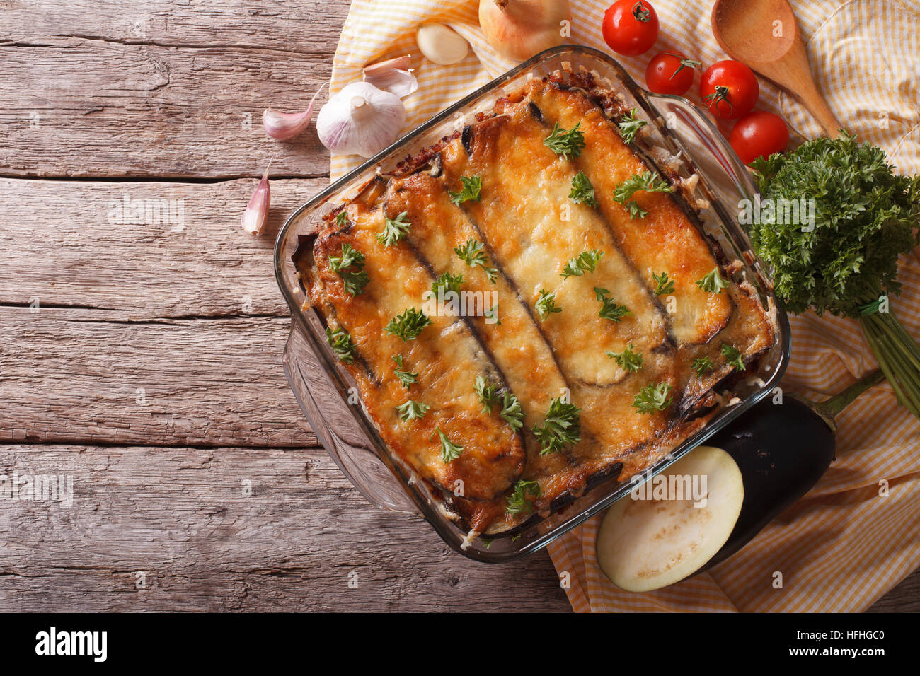 Greek moussaka in baking dish with the ingredients on the table. horizontal view from above - Stock Image