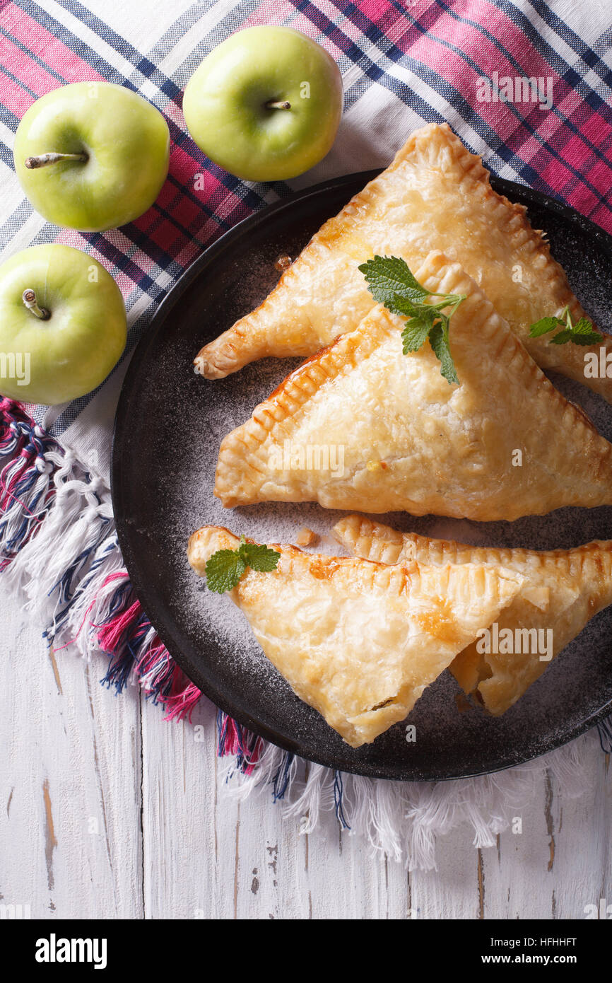 Delicious homemade apple pie turnover close-up on a plate. vertical top view - Stock Image