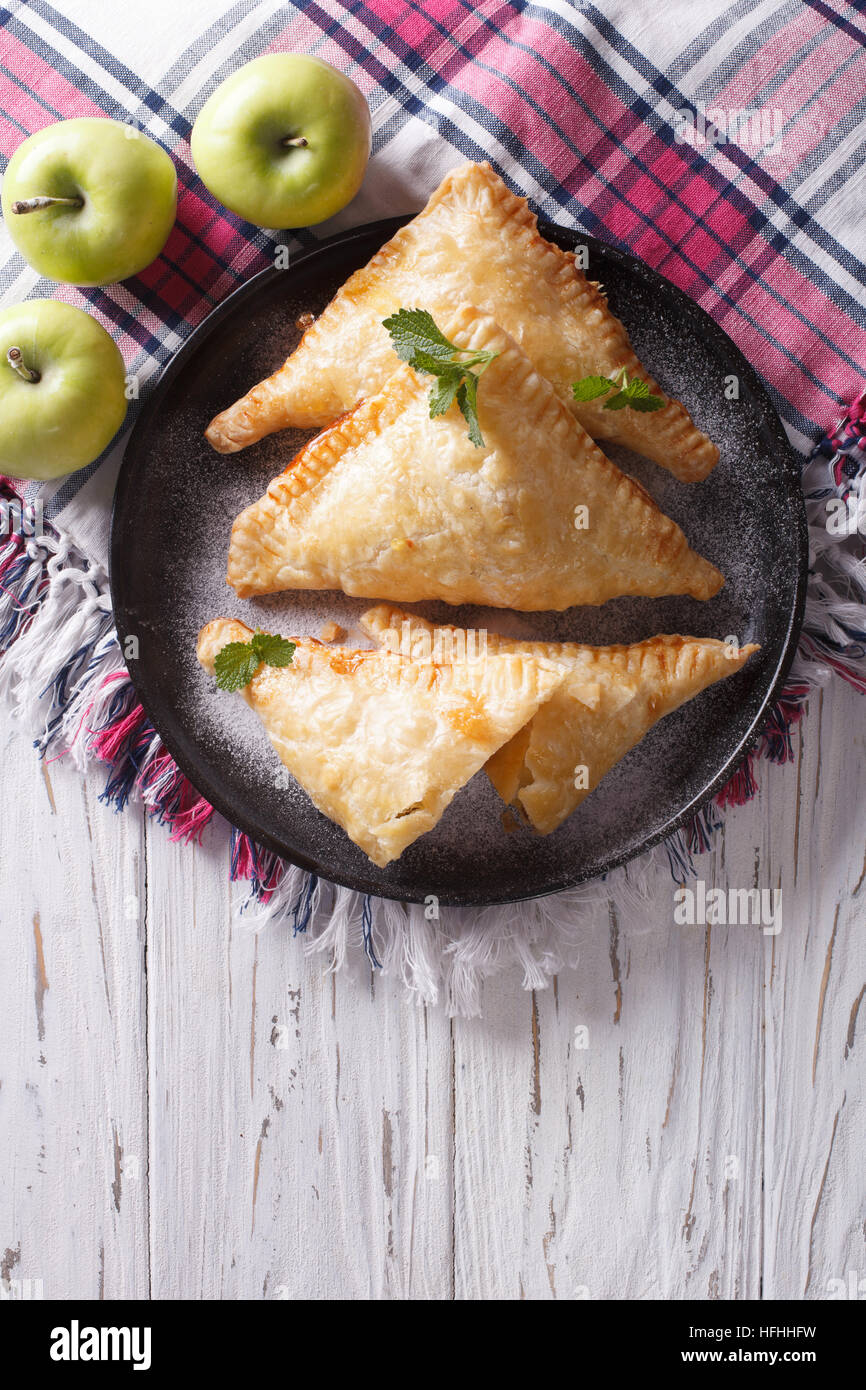 Delicious homemade apple pie turnover on a plate. vertical top view - Stock Image