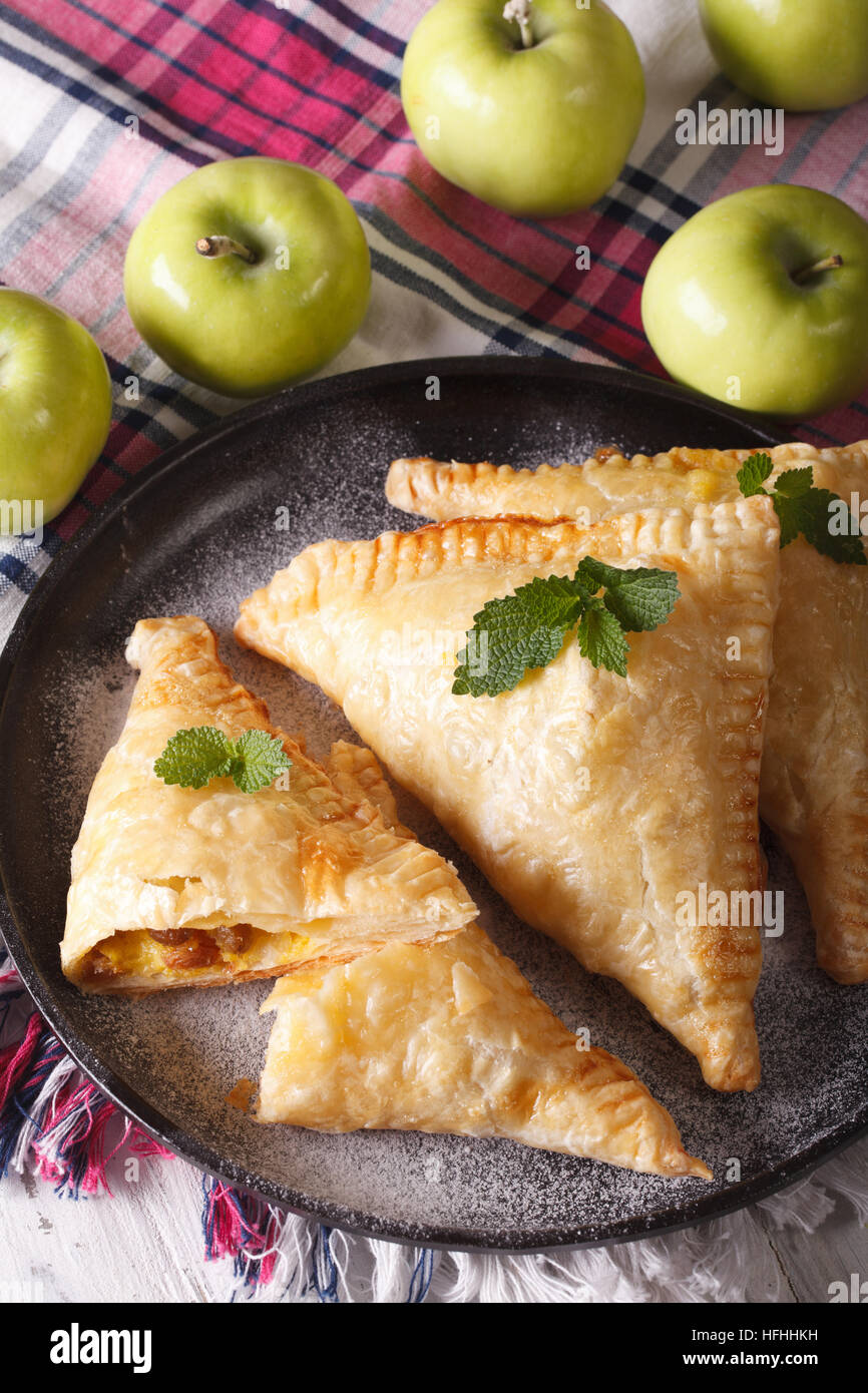 homemade turnover pie with apple filling close-up on a plate. vertical - Stock Image