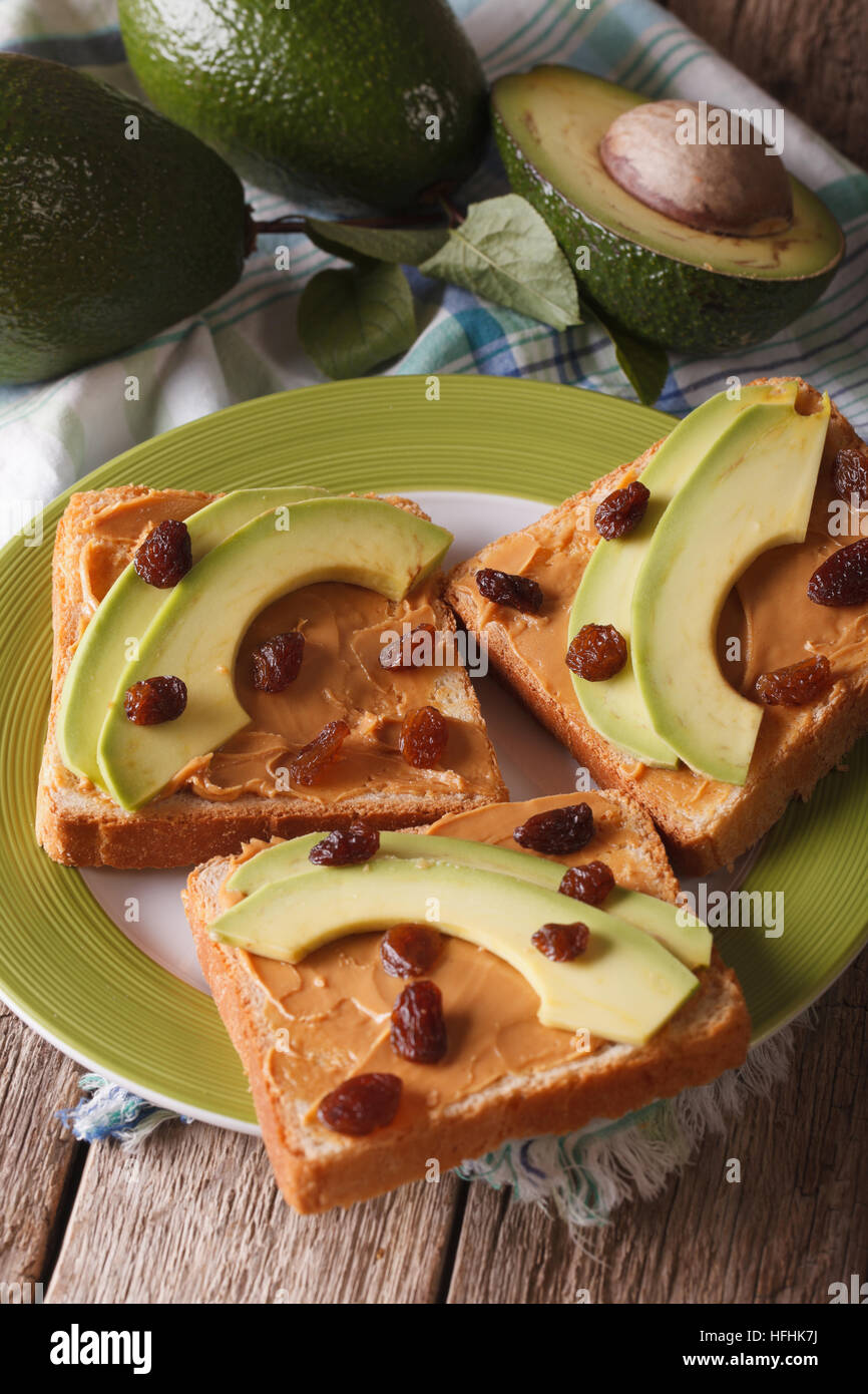 Sandwiches with peanut butter, raisins and ripe avocado close-up on a plate. Vertical - Stock Image