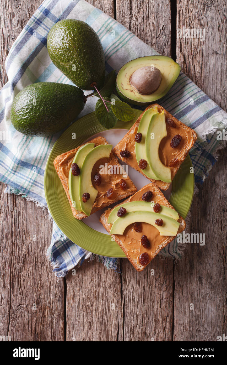 Homemade sandwiches with peanut butter, raisins and avocado on a plate. vertical top view - Stock Image