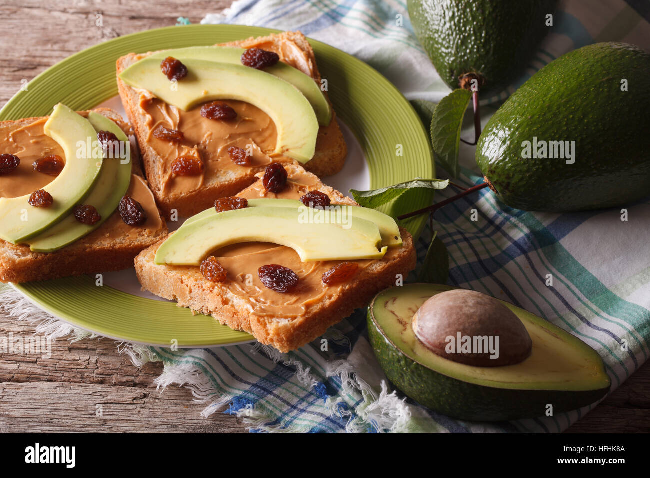 Sandwiches with peanut butter and ripe avocado close-up on a plate. horizontal - Stock Image