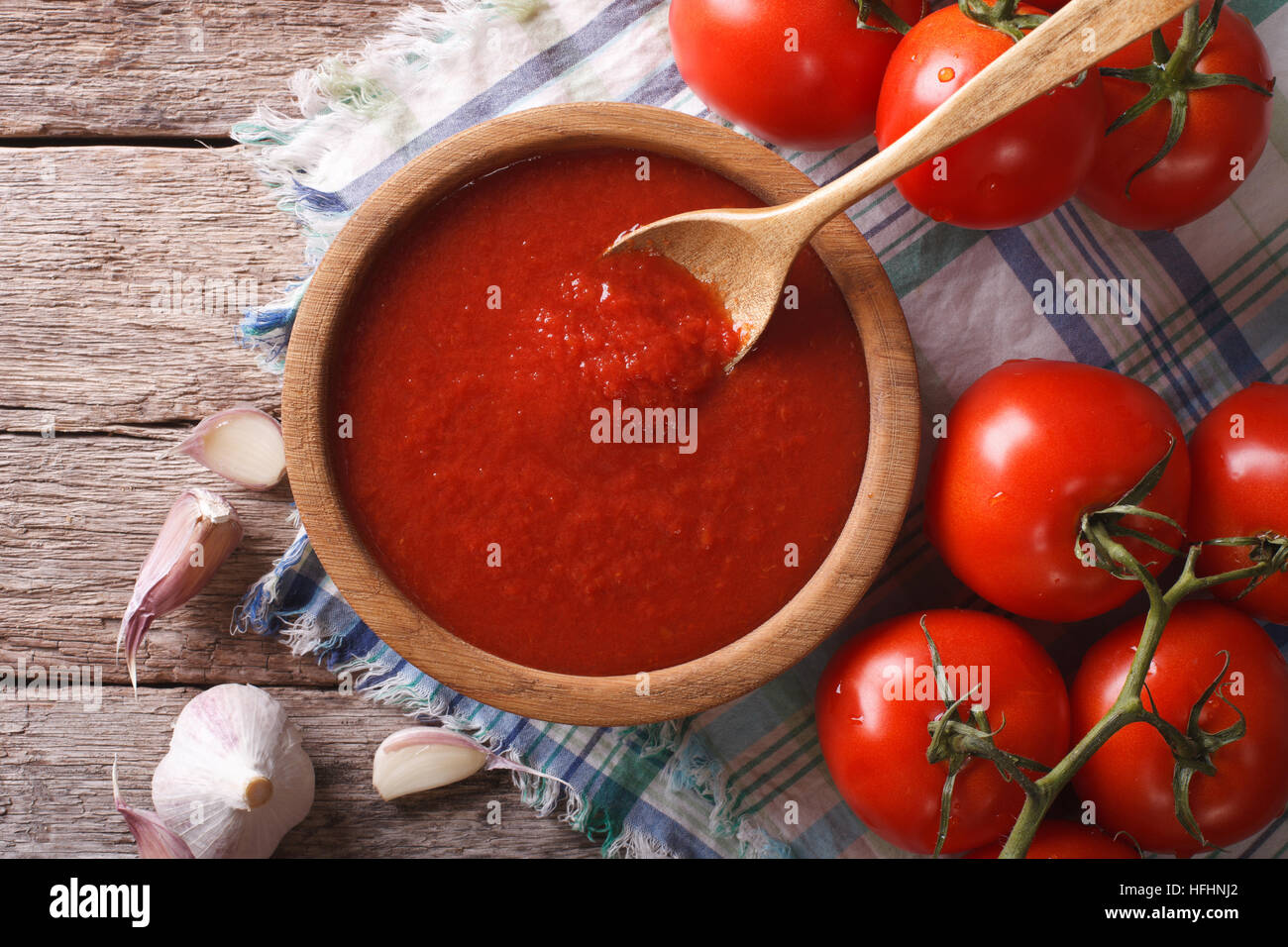 tomato sauce with garlic and basil in a wooden bowl closeup. horizontal view from above - Stock Image