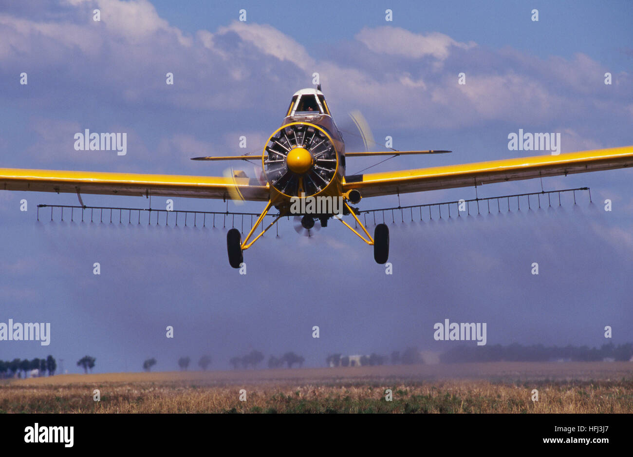 A yellow agricultural crop dusting aircraft sprays a farm field with pesticide. Aerial application, or what was - Stock Image