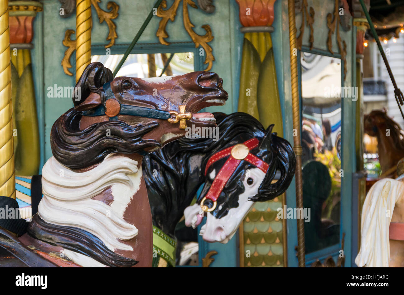 Side view of wooden carousel roundabout horses - Stock Image