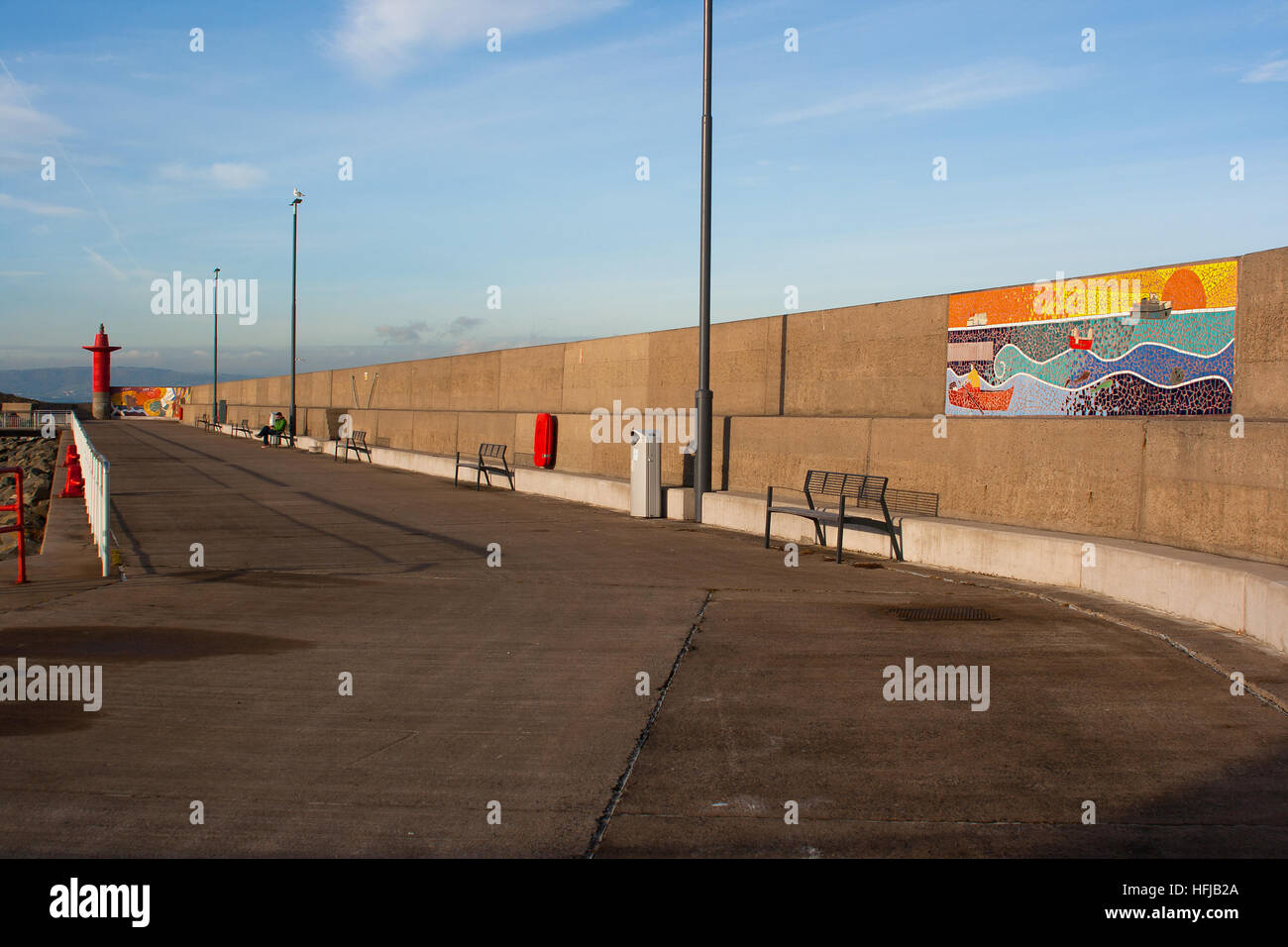 A modern harbor pier built of concrete with a colorful mosaic mural on display and also with navigation lights for - Stock Image