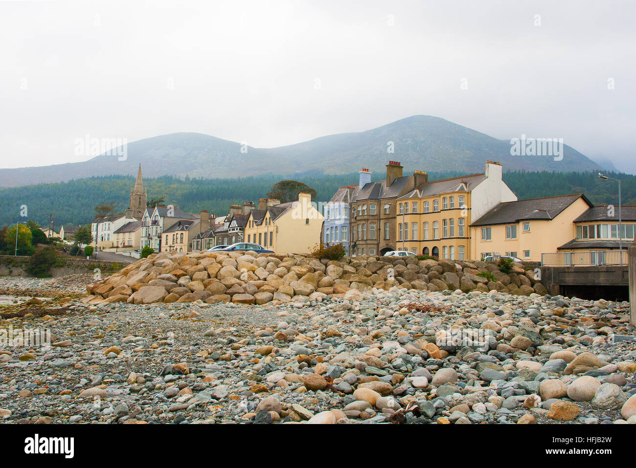 Stony beach front in Newcastle County Down on a misty day with the Mourne Mountains in the backgroundIrish - Stock Image