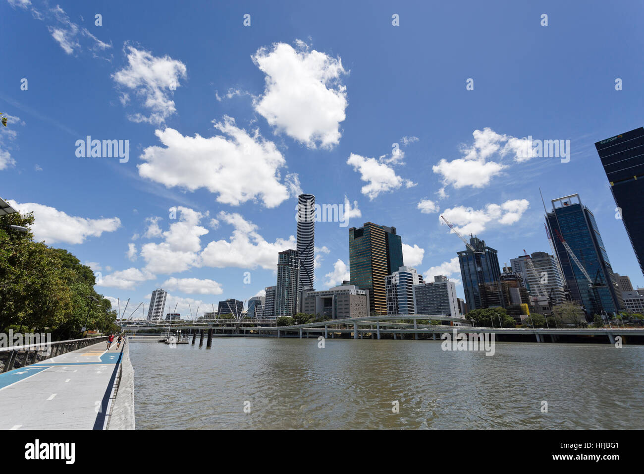 People exercising along the riverside pathway having the Brisbane city in the backgroung - Stock Image