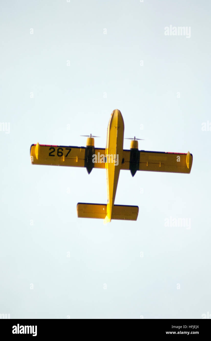 The large water bomer float plane flying above, fighting forest fire in the large state of Alaska during the summer. - Stock Image