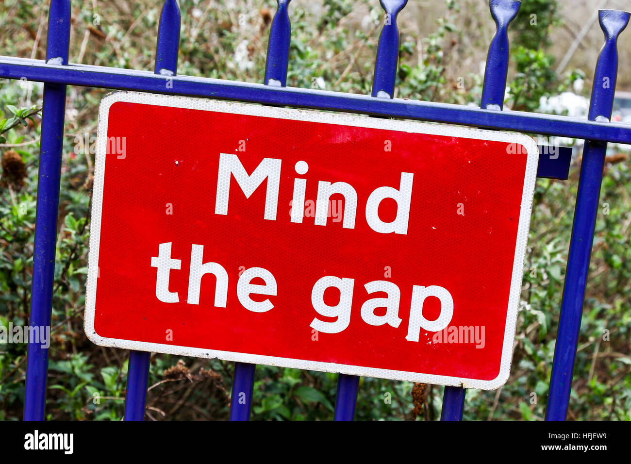A red warning sign saying 'Mind the gap' - Stock Image