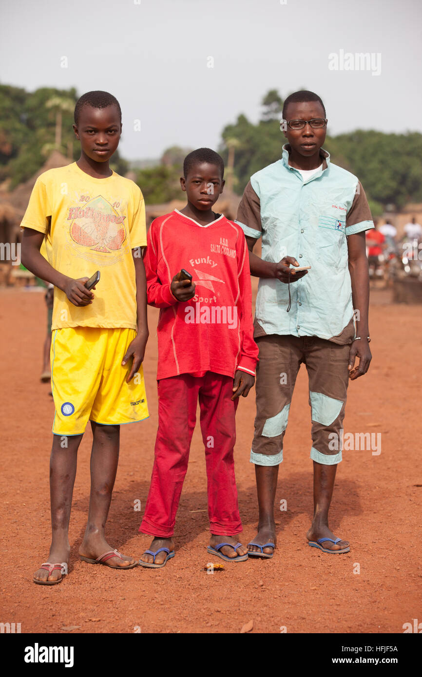 Koumban village, Guinea, 2nd May 2015; Teenagers on the street with their mobile phones. Stock Photo