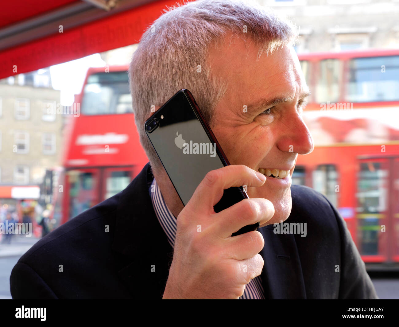 Smiling city businessman sitting at outdoor café talking on his jet black smartphone iPhone 7 plus with typical - Stock Image