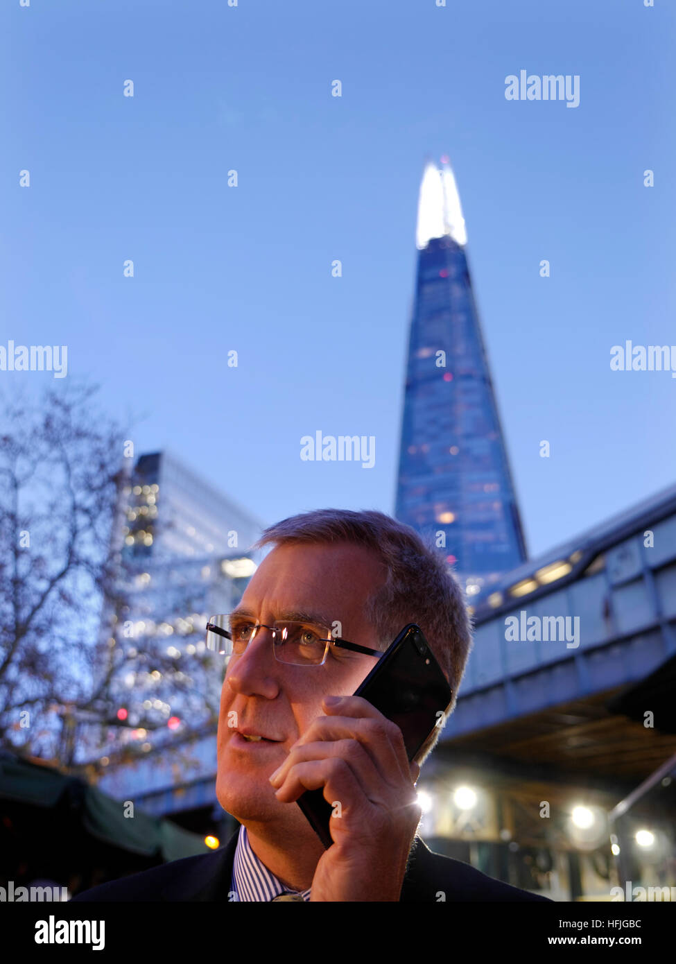 City businessman outdoors talking on his jet black iPhone 7 plus at dusk with 'The Shard' tower in background - Stock Image