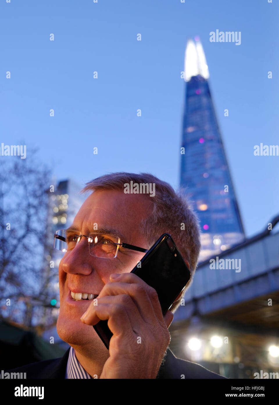 Smiling city businessman outdoors talking on his jet black iPhone 7 plus at dusk with 'The Shard' tower - Stock Image