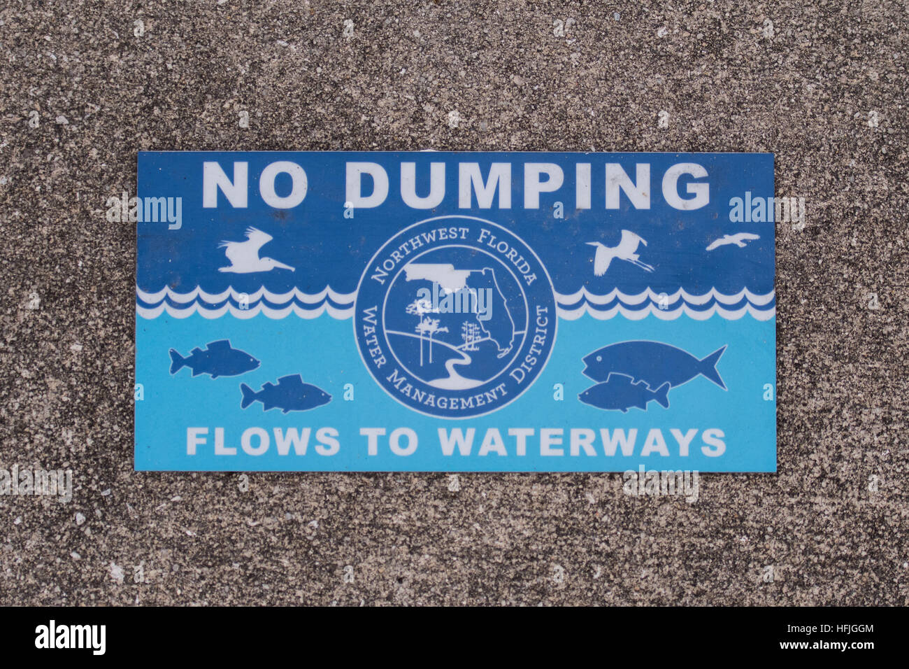 No Dumping Sign in Sidewalk reminds people to protect the local water - Stock Image