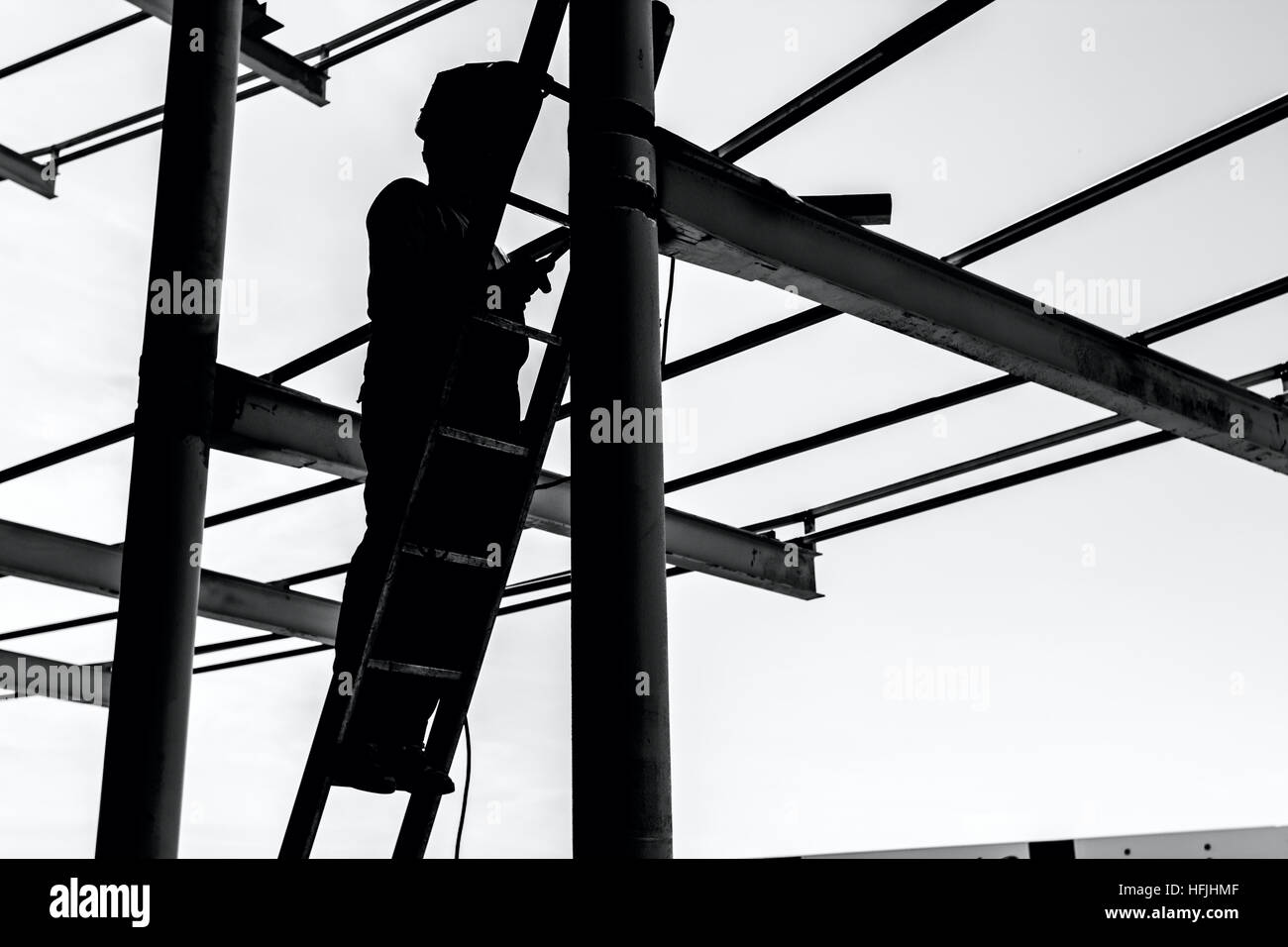 Silhouetted industrial shot of construction worker who is using the wooden ladder to welding metal frame. - Stock Image