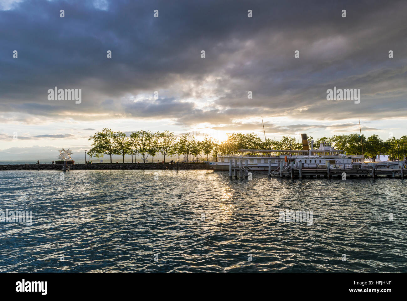 Late sun through clouds over a paddle steamer at the port of Ouchy, Lausanne, Vaud, Switzerland - Stock Image