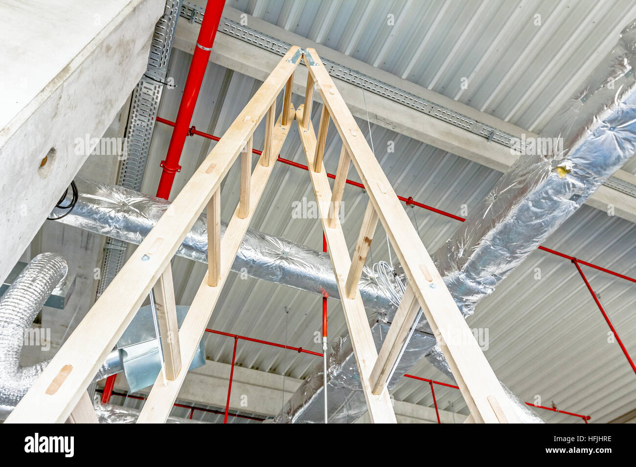 Wooden stepladder and fire fighting system is placed on the ceiling. Stock Photo