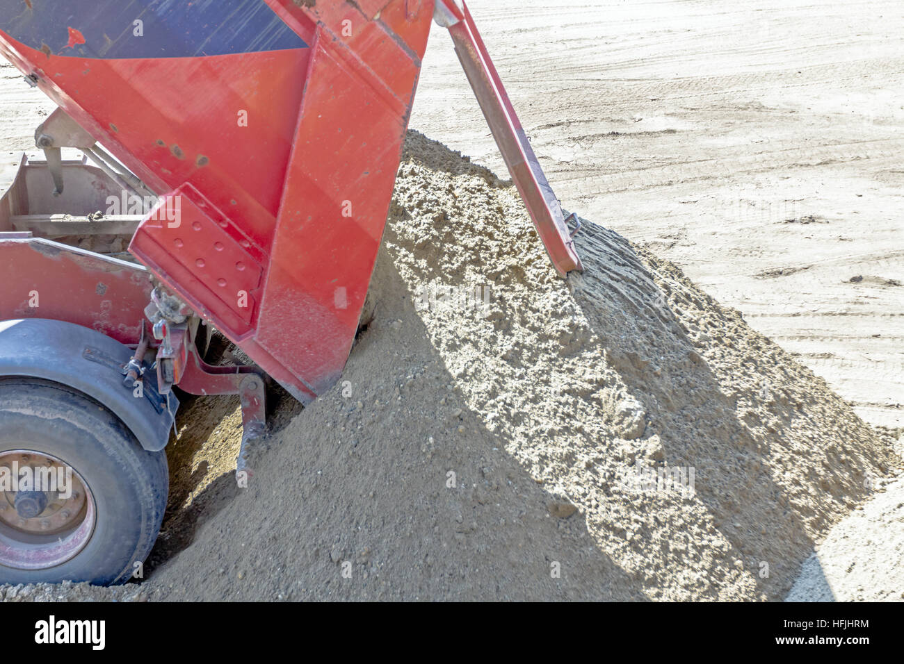 Red dumper truck is unloading sand at construction site. - Stock Image