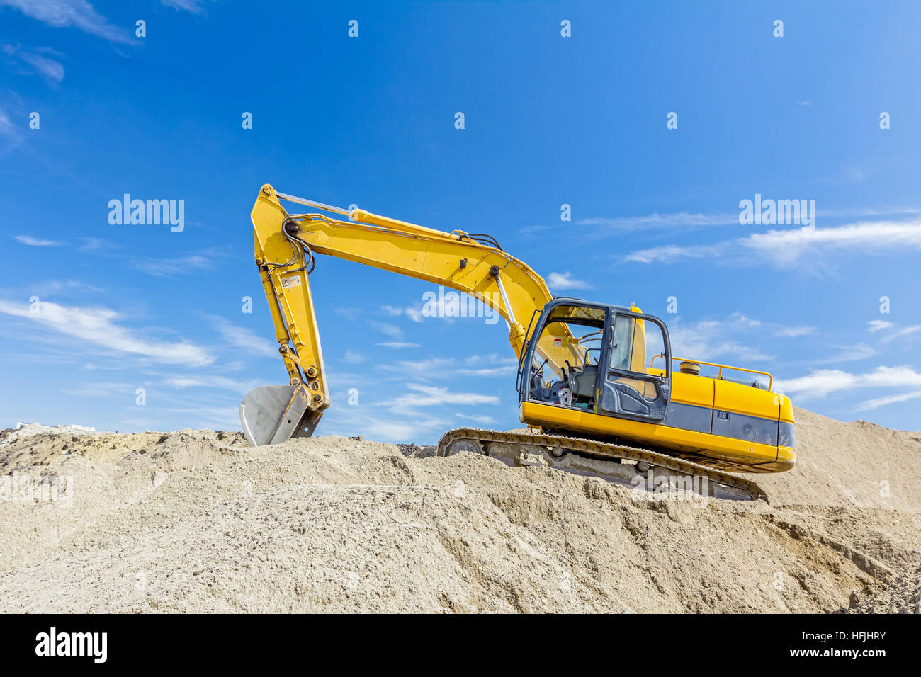 Yellow excavator is making pile of soil by pulling ground up on heap at construction site, project in progress. Stock Photo