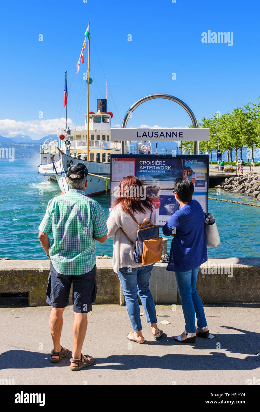 Tourists looking at a information board as a paddle steamer arrives in Lausanne, Vaud, Switzerland - Stock Image