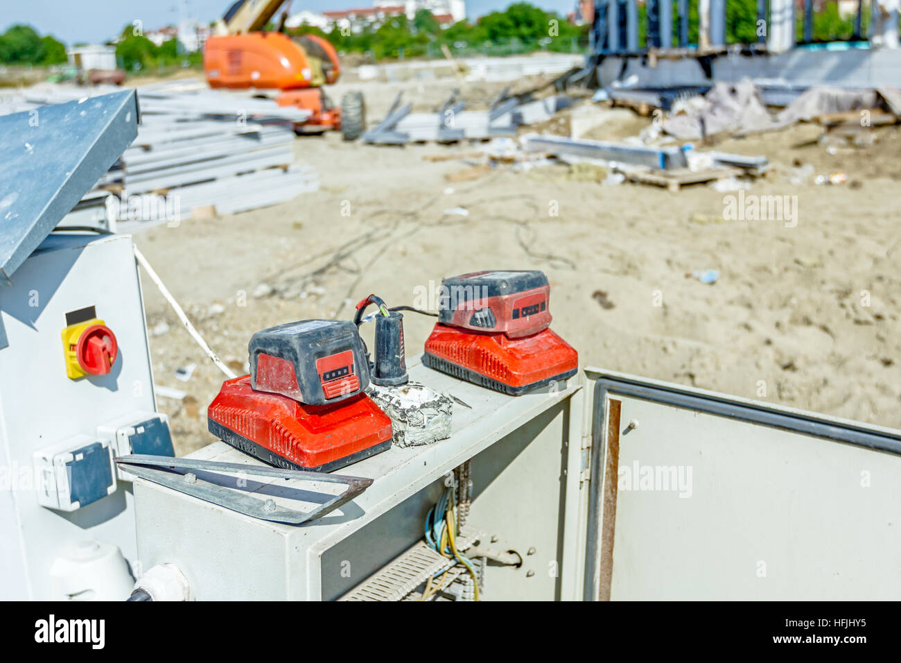 Charging rechargeable battery over power charger, for cordless tools. Fuse box on building site. - Stock Image