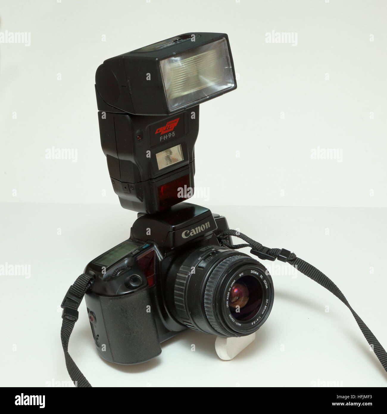 Canon EOS 100 35mm SLR film camera with Sigma 35-80mm lens and Centon FH95 flashgun in forward facing position from - Stock Image