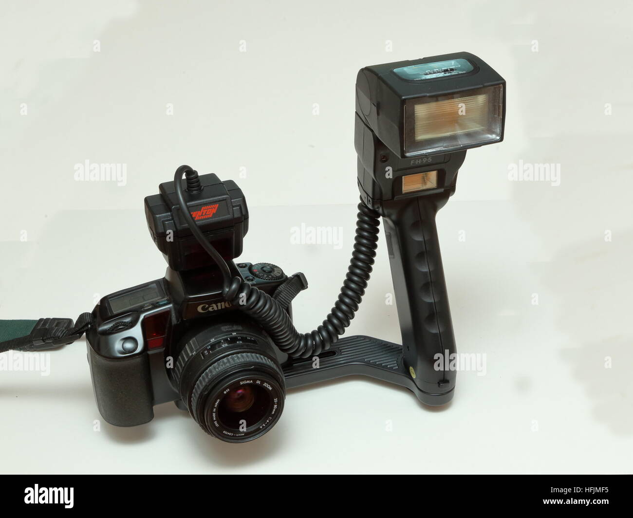 Canon EOS 100 35mm SLR film camera with Sigma 35-80mm lens and Centon FH95 flashgun on hand grip from 1990s - Stock Image