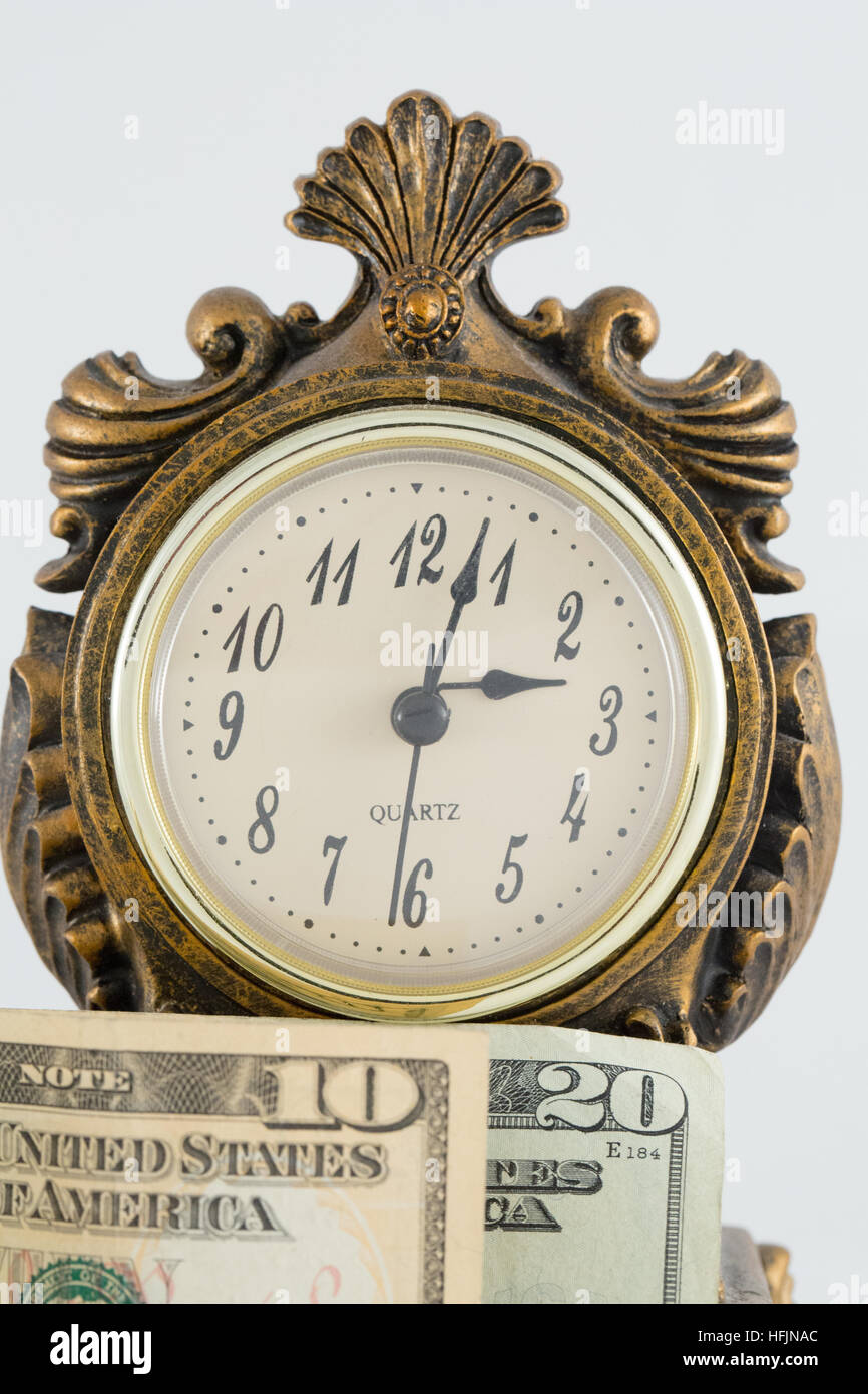 Old clock with money in front of it. - Stock Image