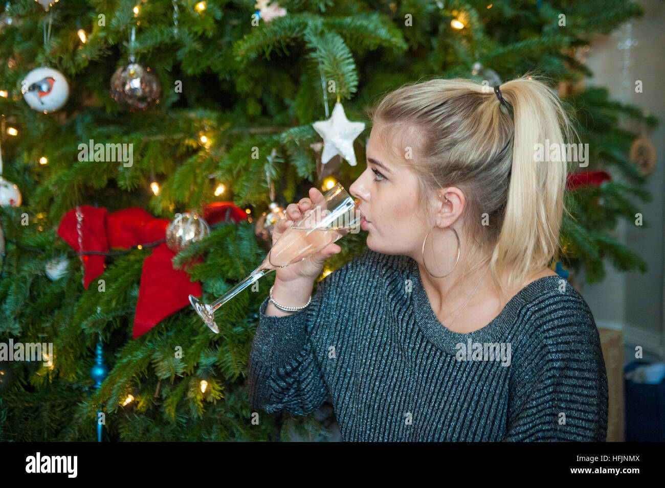 A pretty blond girl by a Christmas tree - Stock Image