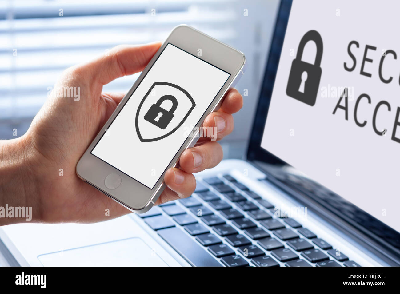 Cyber security symbol with icon of shield and lock on the screen of mobile phone and notebook computer Stock Photo