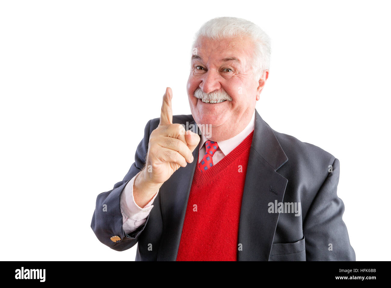 Close up of cheeky senior wearing a business suit with red sweater smiles at the camera and points up - Stock Image