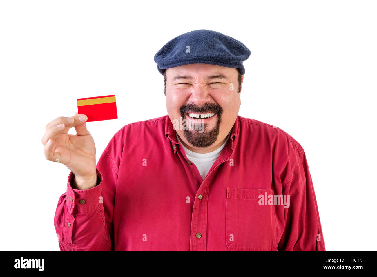 Gleeful middle-aged man with a goatee wearing a red shirt and cap holding up a bank card with a beaming smile and - Stock Image
