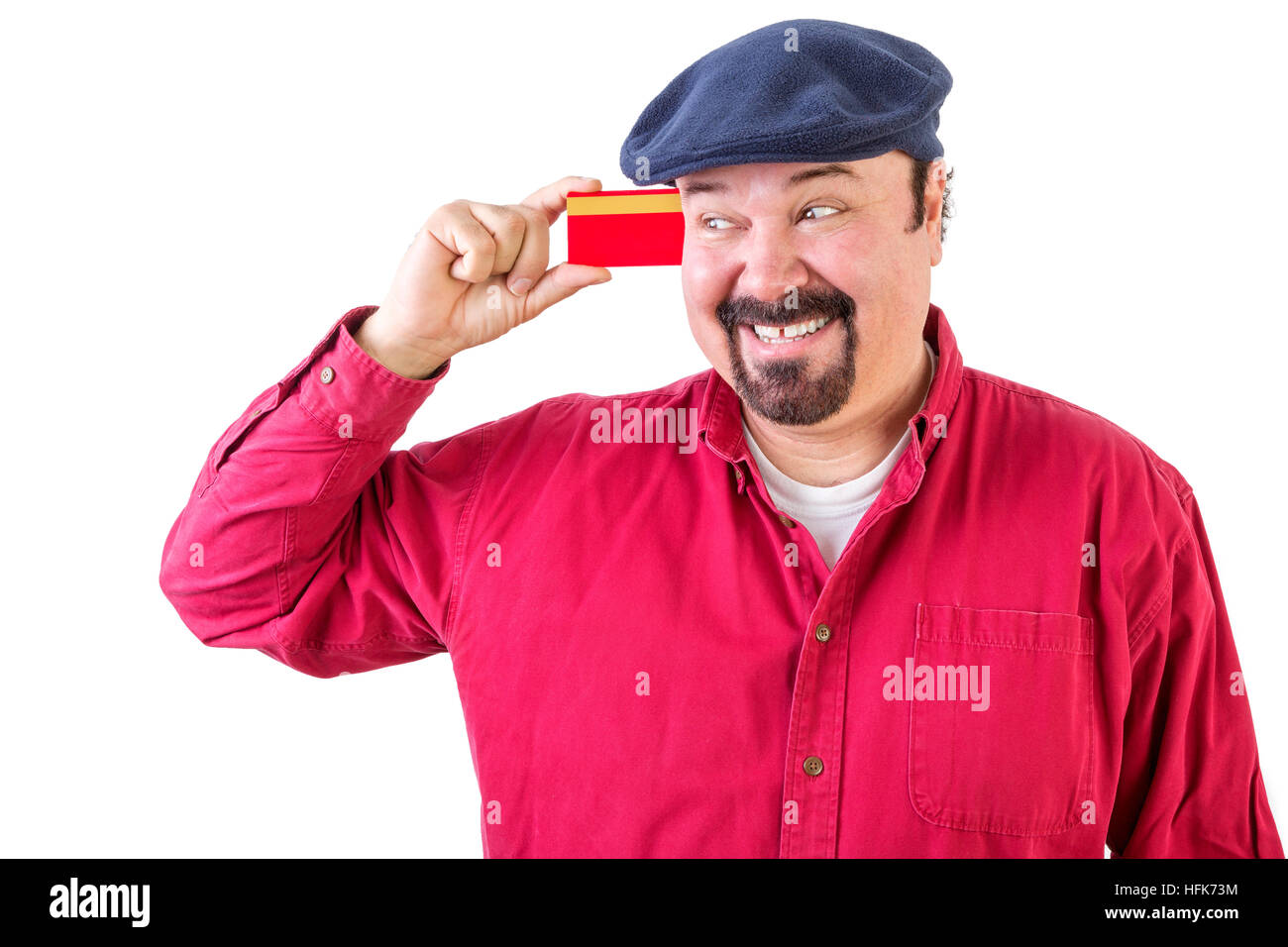 Gleeful man eyeing his credit card with a beaming smile of anticipation as he imagines all the things he can go - Stock Image