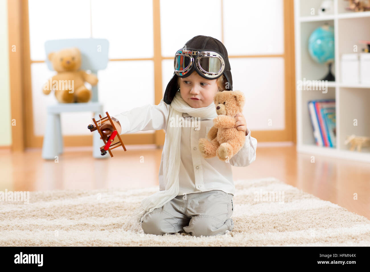 Happy kid boy plays with toy airplane at home in his room - Stock Image