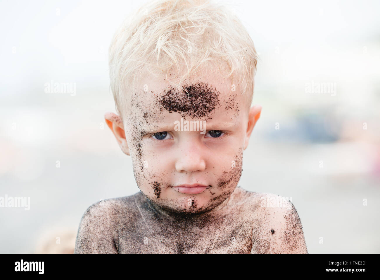 Funny happy baby boy on beach with dirty face covered with black sand. Family travel, healthy children lifestyle - Stock Image