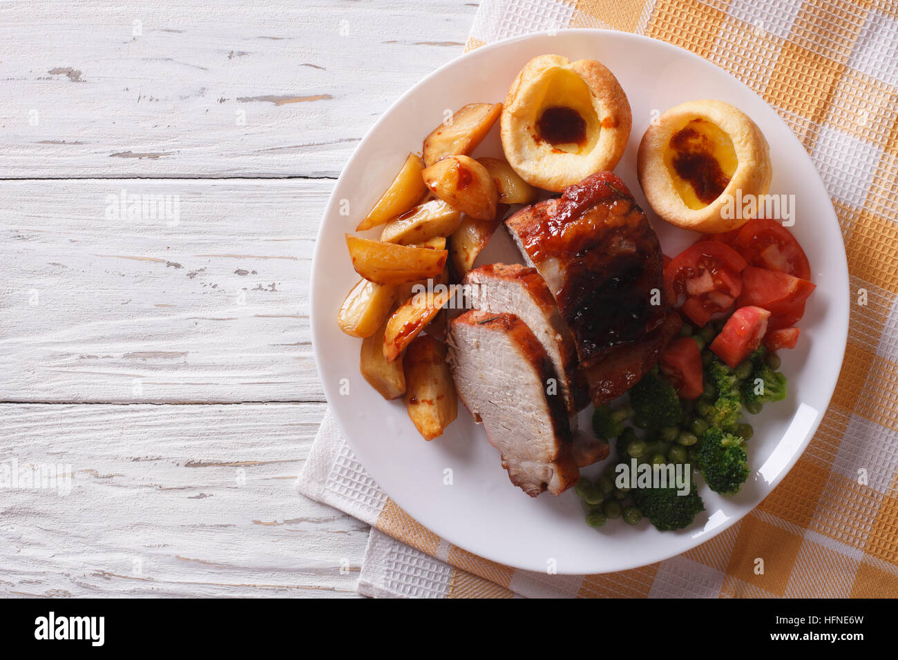 Sunday Roast: pork with potatoes, vegetables and Yorkshire pudding close up on the table. horizontal view from above - Stock Image