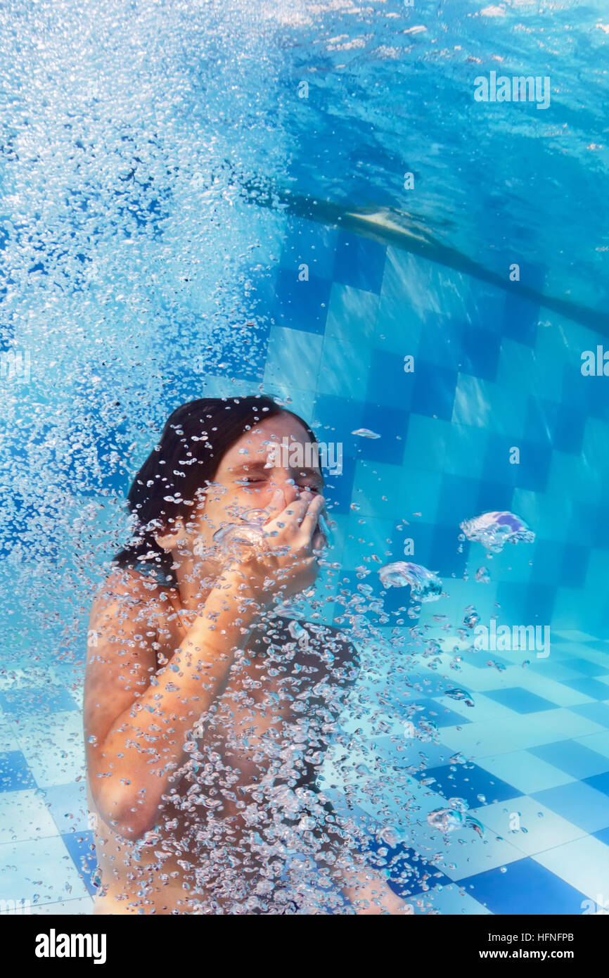 Funny portrait of boy swimming and diving in blue pool with fun - jumping underwater with splashes and foam. Family - Stock Image