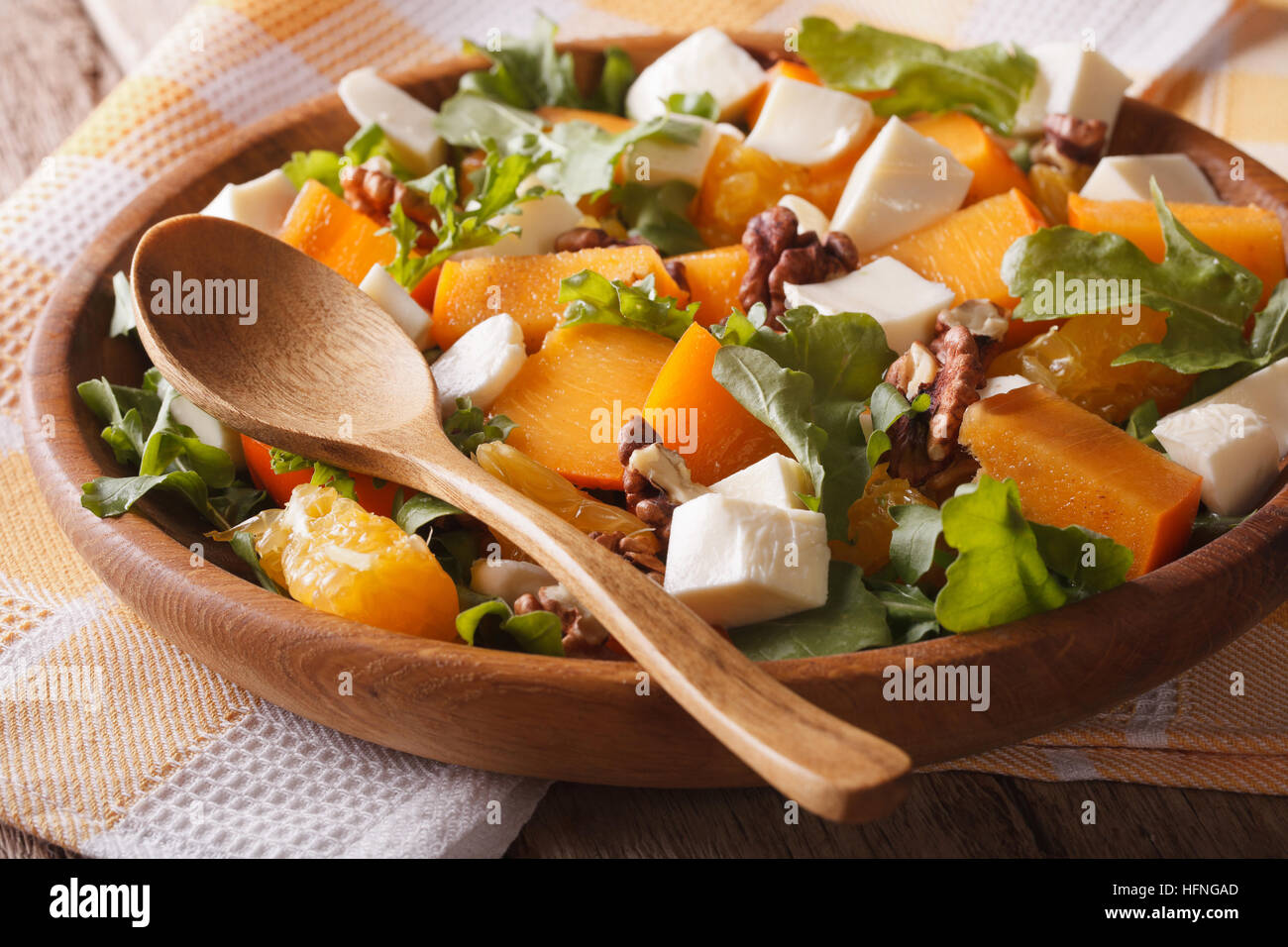 Fresh salad with persimmons, walnuts, arugula, cheese and oranges close-up. Horizontal, rustic Stock Photo
