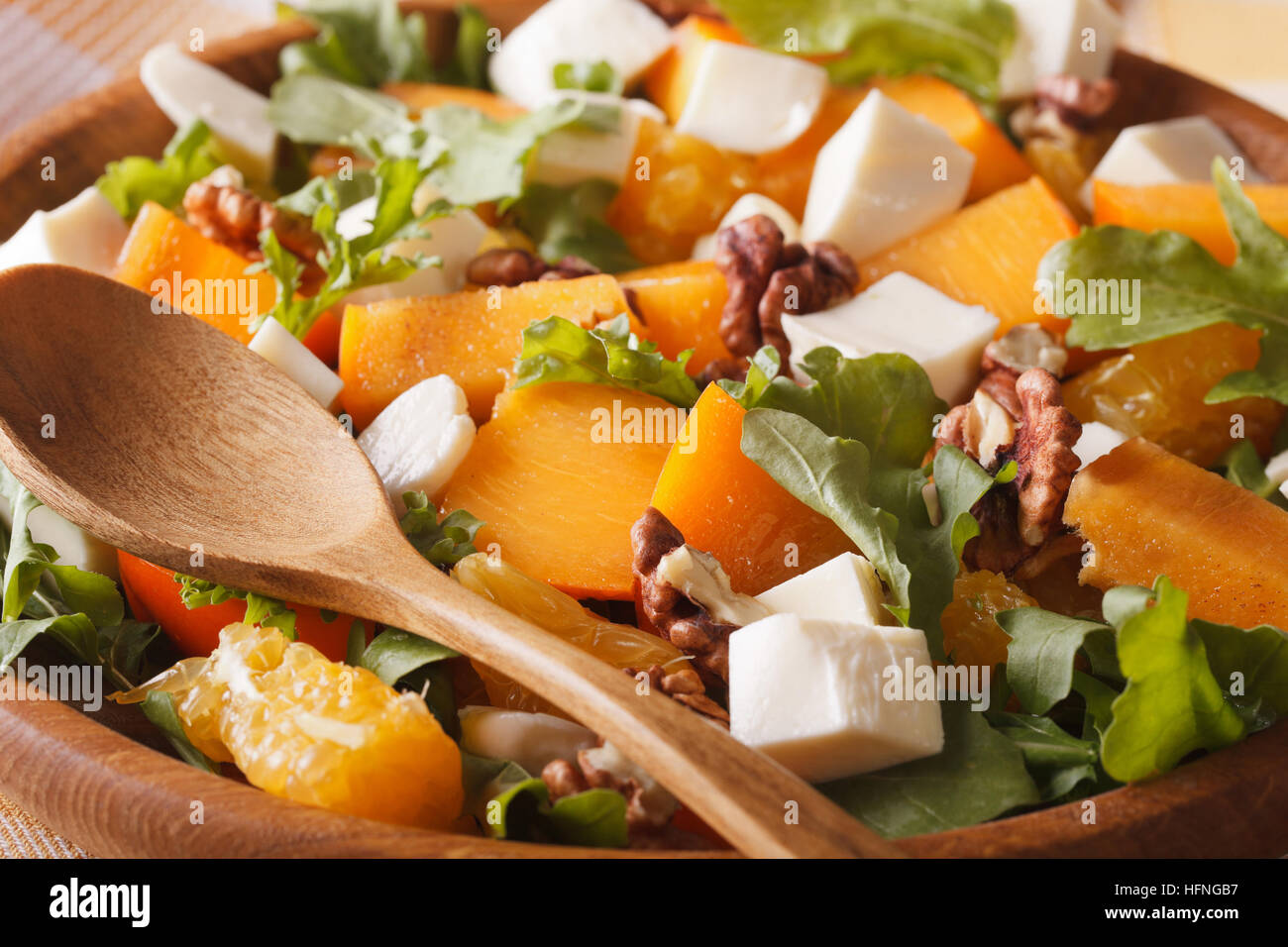 Healthy salad with persimmons, walnuts, arugula, cheese and oranges macro. horizontal - Stock Image