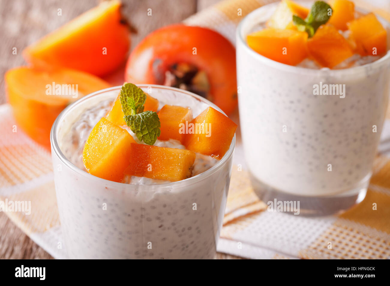 dessert with chia seeds and persimmon close up in a glass on the table. Horizontal - Stock Image