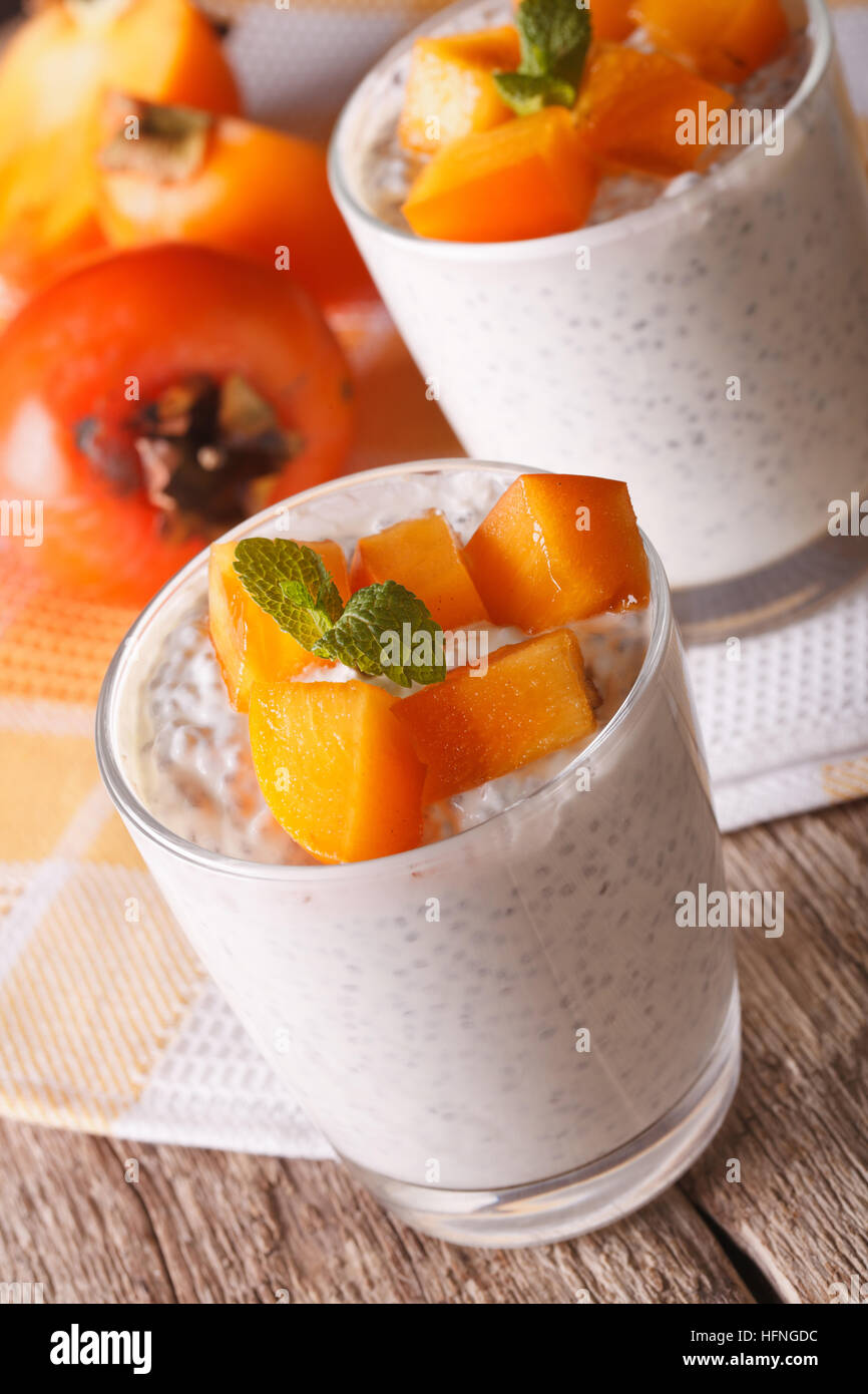 Healthy Food: dessert with chia seeds and persimmon close up on the table. vertical - Stock Image
