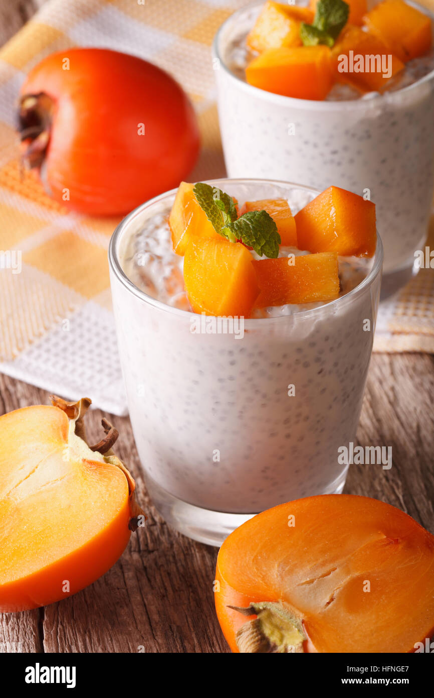 Healthy breakfast: chia seed pudding and persimmon close-up on the table. vertical - Stock Image