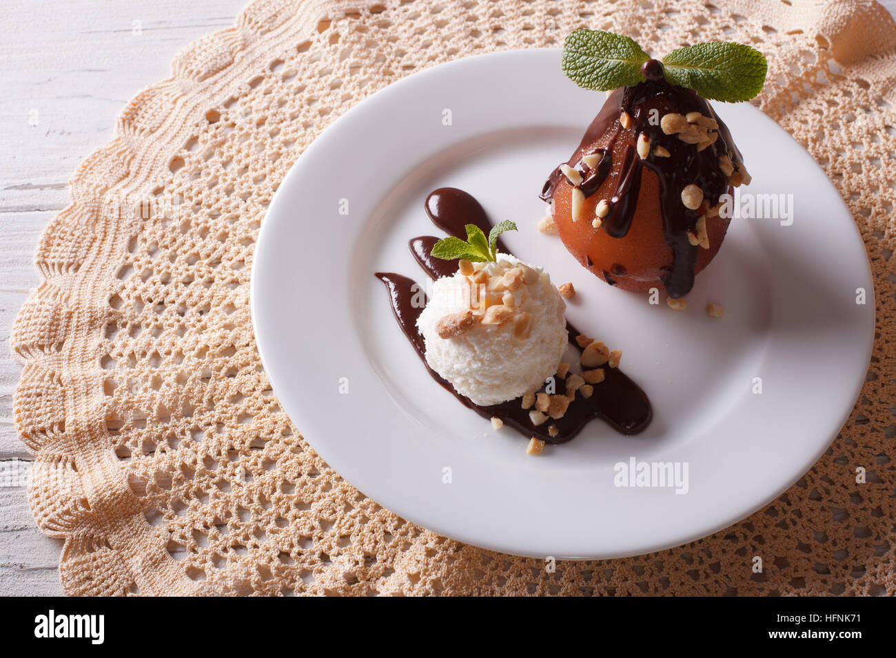 Delicious food: poached pear with chocolate and ice cream on a plate. top view horizontal - Stock Image