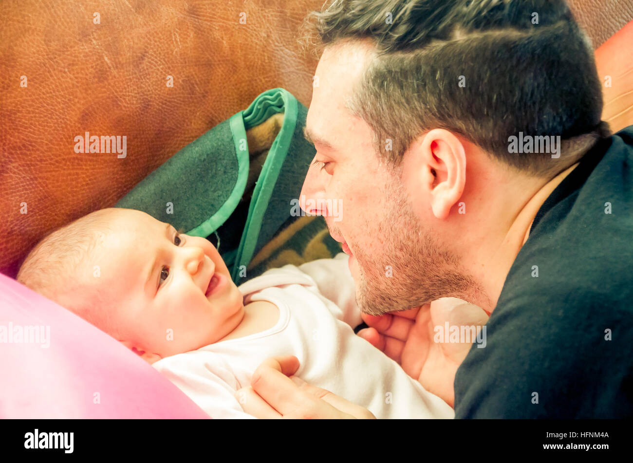 Dad makes faces grimacing newborn baby laughs - Stock Image