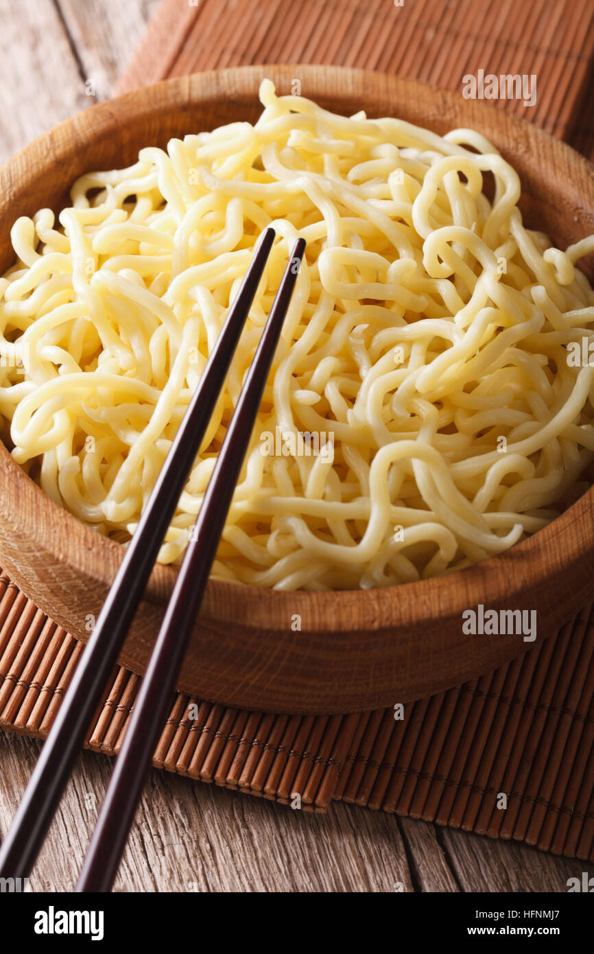 Asian fast food: Ramen in a wooden bowl on the table close-up. Vertical Stock Photo