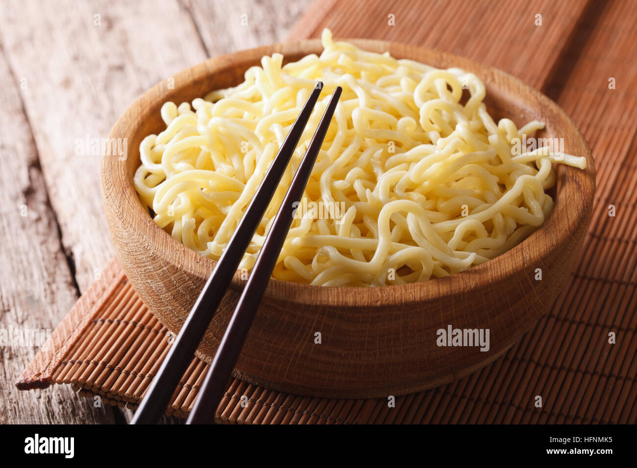 Asian fast food: Ramen in a wooden bowl on the table close-up. horizontal Stock Photo