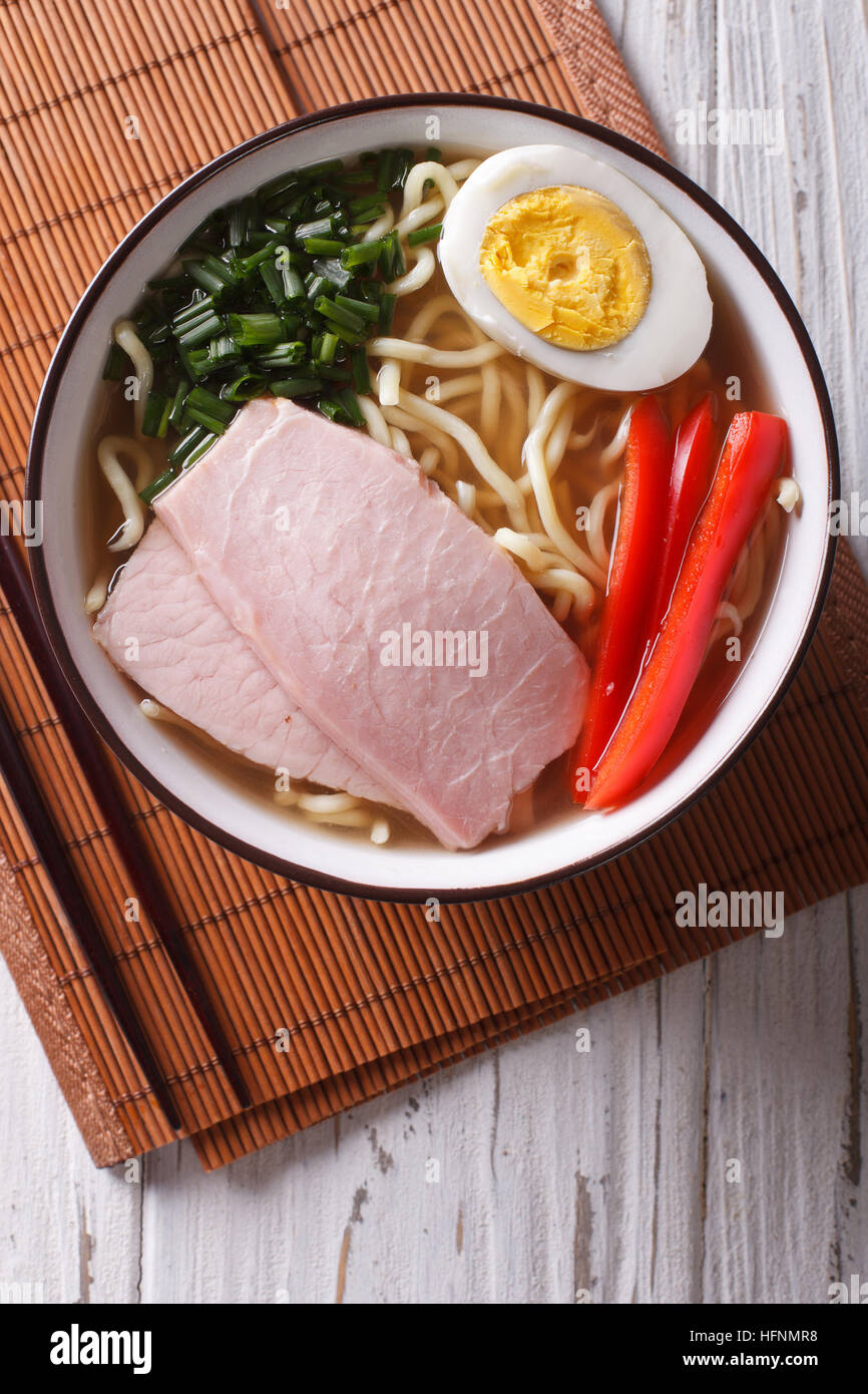 Ramen noodles in broth with pork, vegetables and egg in a bowl close up. vertical top view - Stock Image